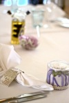 Dining table set with menus, flowers in theme colours, standard glassware, linens and cutlery. Wedding favours provided by client.